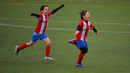 Dos niños celebrando un gol.