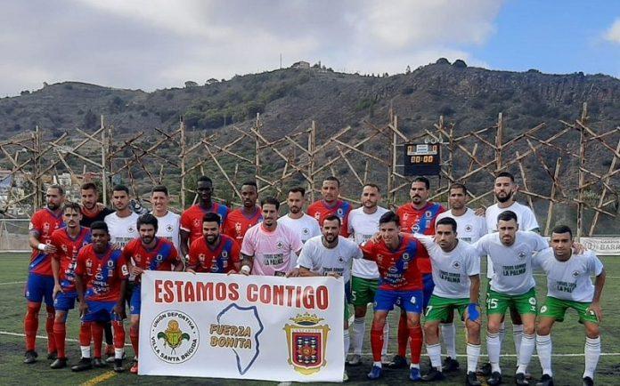Jugadores de ambos equipos con una pancarta de ánimo a la isla de La Palma